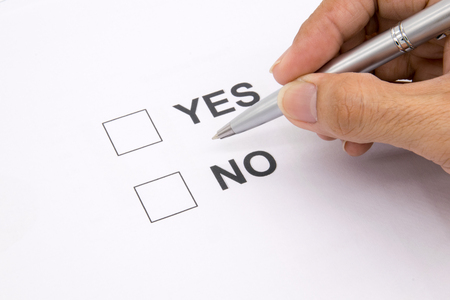 Man hand with pen over document, select Yes or No.
