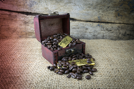 coffee table: Old wooden chest with Coffee beans and Gold Bullion, on Sackcloth background Stock Photo