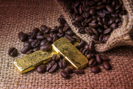 gold table cloth: Coffee beans and Gold Bullion in sackcloth bag on wooden background Stock Photo
