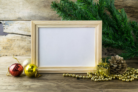 Picture Frame and Christmas decorations on old wooden background. Standard-Bild