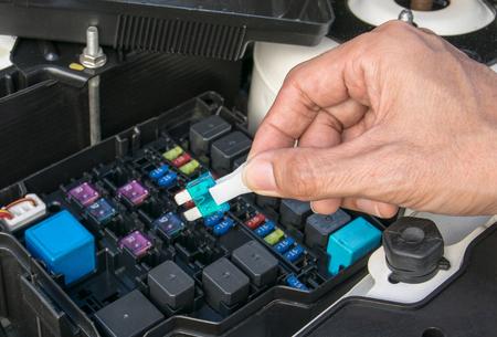 Mecánico auto que controla un fusible de coche