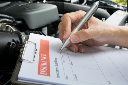 filling in: Mechanic Inspecting damage car and filling in accident report form