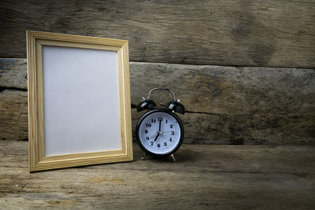 Wood photo frame and clock on wooden table