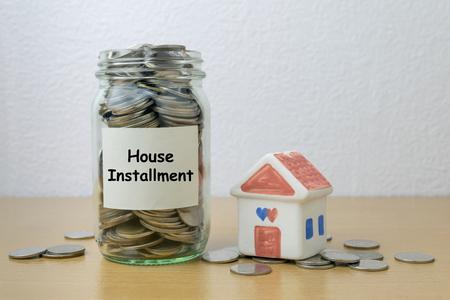 installment: Money saving for house installment in the glass bottle Stock Photo