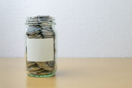 money jar: Money jar with coins on wood table