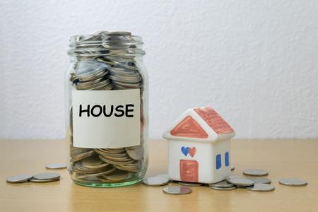 installment: Money saving for house in the glass bottle Stock Photo