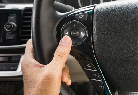 pushes: hand pushes the cruise control button on a steering