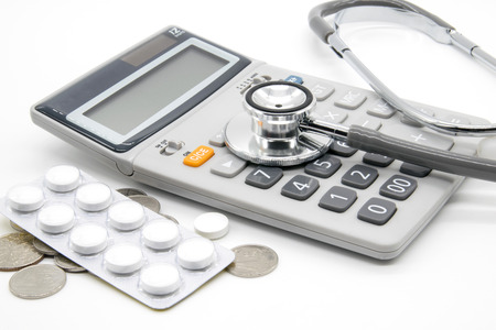 health care fees: Calculator and stethoscopes on white background