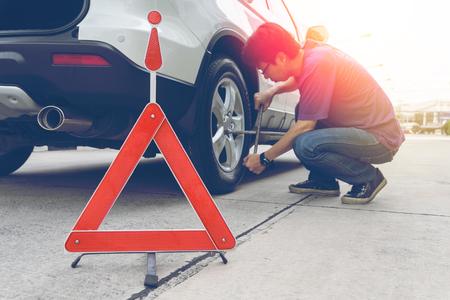 man nuts: Man loosening lug nuts on his car flat tire. broken down car
