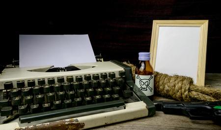 suspenso: Máquina de escribir con la página de papel y el veneno y la pistola. Concepto escritor Romance Suspenso