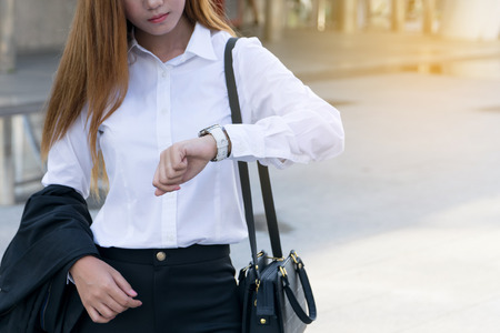 Young business woman checking the time on her watch. Stock Photo