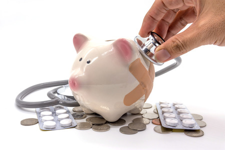 Doctor Holding Stethoscope to Piggy Bank