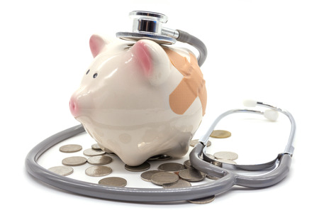 stethoscope with pink piggy bank and coins Stock Photo