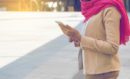 Muslim woman messaging on a mobile phone in the city