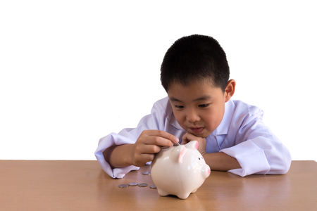 Asian boy playing as a doctor balance money in Piggy Bank, isolated background with clipping path. Stock Photo