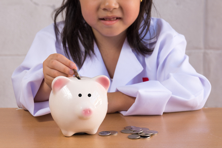 Asian girl playing as a doctor balance money in Piggy Bank Stock Photo
