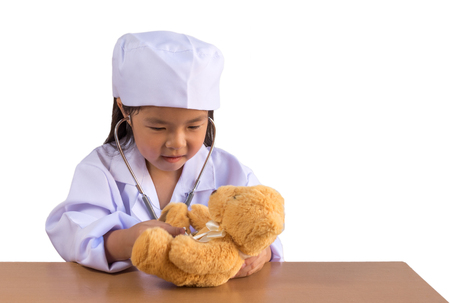 Asian girl playing as a doctor care bear doll, isolated background with clipping path. Imagens