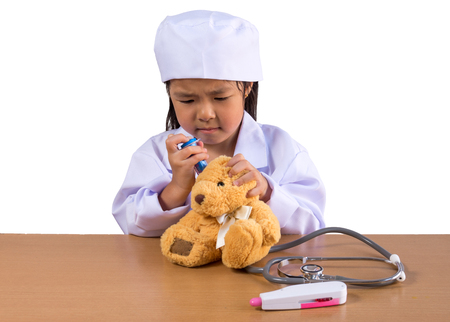 Asian girl playing as a doctor care bear doll, isolated background with clipping path. Stock Photo