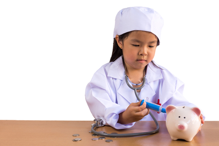 Asian girl playing as a doctor care Piggy Bank, isolated background with clipping path.