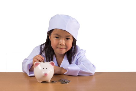 Asian girl playing as a doctor balance money in Piggy Bank, isolated background with clipping path.