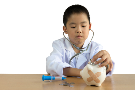 Asian boy playing as a doctor care Piggy Bank, isolated background with clipping path.