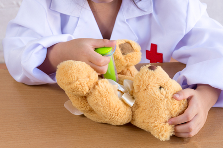 Asian girl playing as a doctor care bear doll
