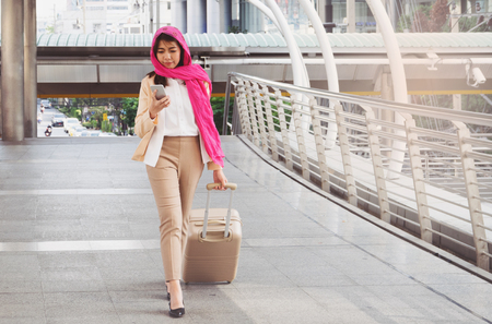 Arabische Frau zu Fuß mit einem Koffer Lizenzfreie Bilder
