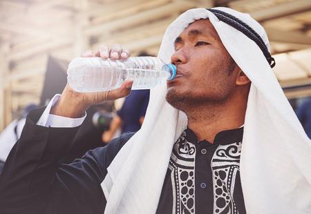 Arabischer Mann trinkt Wasser aus Plastikflasche Lizenzfreie Bilder
