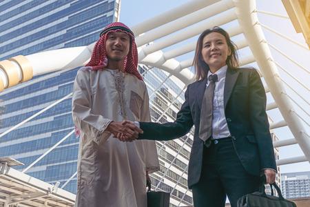 Arabischer Geschäftsmann und Geschäftsfrau Handshaking in der Stadt Lizenzfreie Bilder
