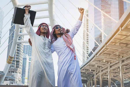Two Arab businessmen standing by raising both hands up in city, Business good feeling concept Lizenzfreie Bilder