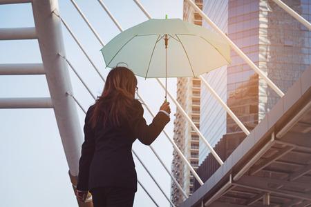 Geschäftsfrau hält einen Regenschirm in der Stadt