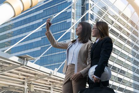 Happy businesswomen making selfie photo at city