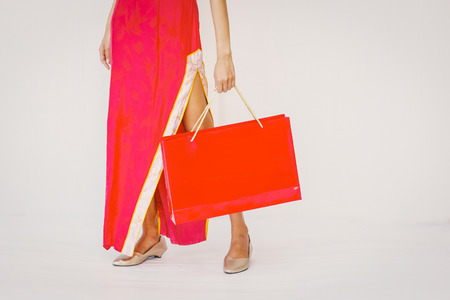 Asian woman holding shopping bag, woman wear cheongsam, chinese new year