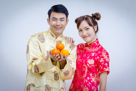 Happy Young couple holding orange. Chinese new year.