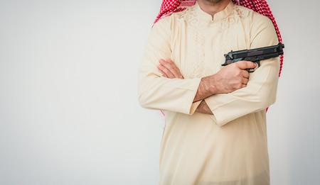 Arab man standing with hand holding gun