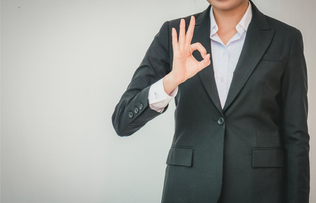 businesswoman pointing up ok hand sign