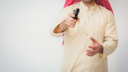 Arab man standing with hand holding gun