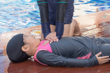 Boy helping drowning child girl in swimming pool by doing CPR. Reklamní fotografie