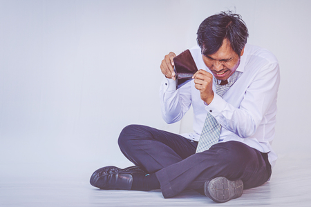 Businessman holding empty wallet sitting on the floor