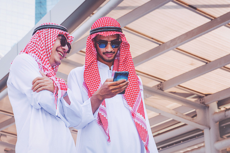 Two Arab businessmen messaging on a mobile phone in city