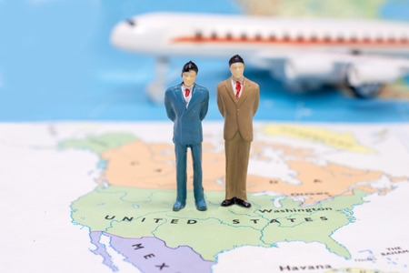 Miniature people, businessman standing on map American 스톡 콘텐츠