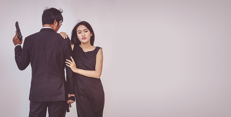 Young couple hugging and posing with gun