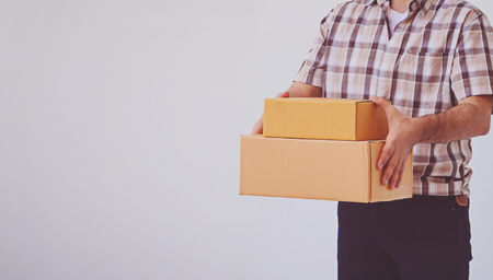 Asian young man holding box package, delivery man
