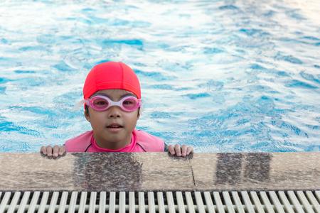 giovane ragazza che nuota in piscina.