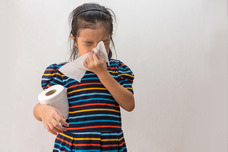 Asian girl sick with sneezing on nose and cold cough on tissue paper