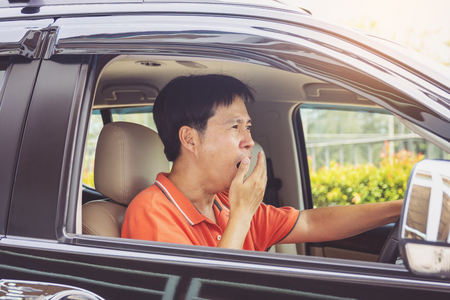 Tired young asia man driving his car Stock Photo