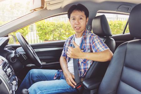 Asia uomo allacciare la cintura di sicurezza in auto