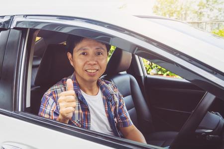 L'homme asiatique sourit heureux et conduit une voiture
