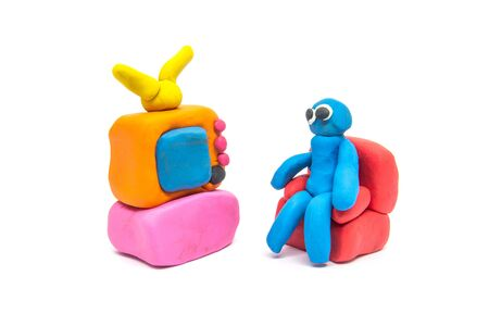 Play dough man sitting on red sofa on white background