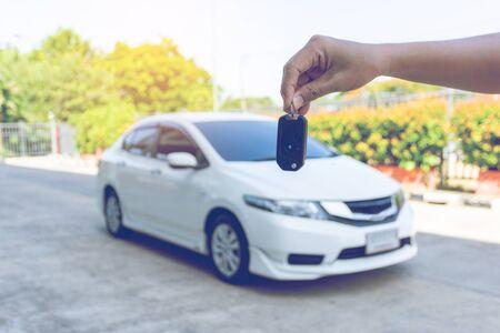 Man holding car keys with car on background
